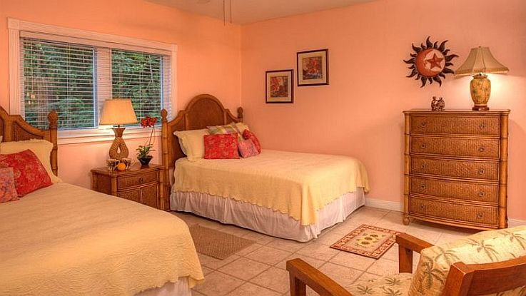 the aqua room is colorfully decorated has two twin beds and will